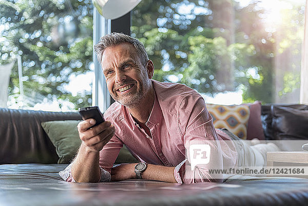 Smiling mature man lying on couch at home using remote control