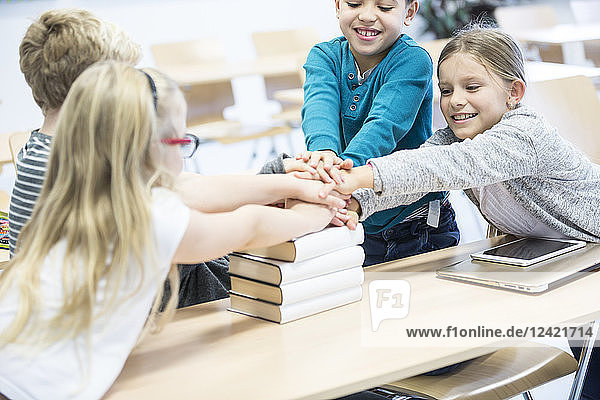 Happy pupils stacking hands on books in class