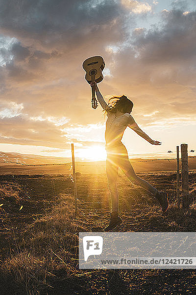 Iceland  woman jumping with guitar at sunset