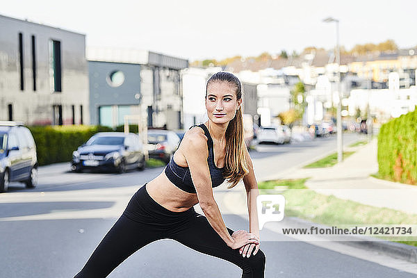 Sportive young woman stretching on a street in the city