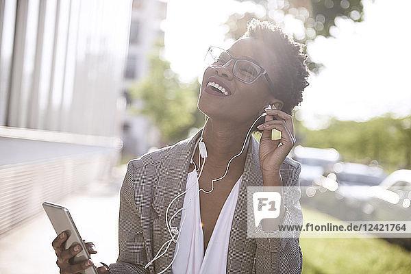 Portrait of happy businesswoman using smartphone and earphones Portrait of happy businesswoman using smartphone and earphones