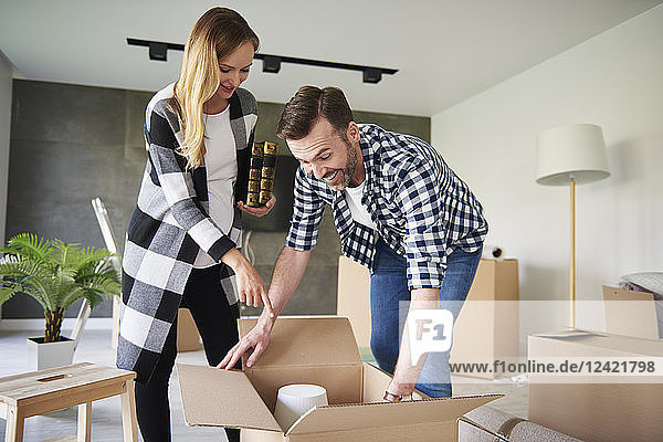 Happy couple moving into new flat unpacking cardboard box
