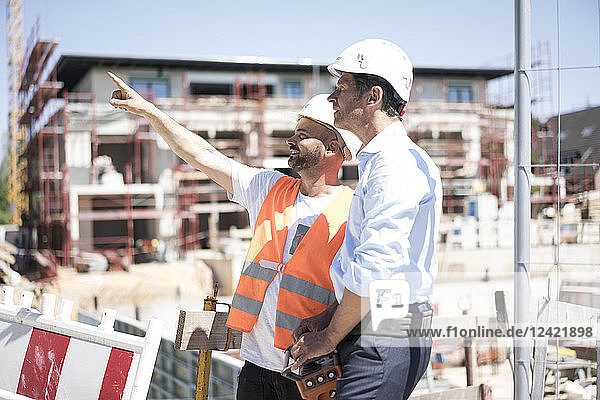 Construction worker talking to man on construction site