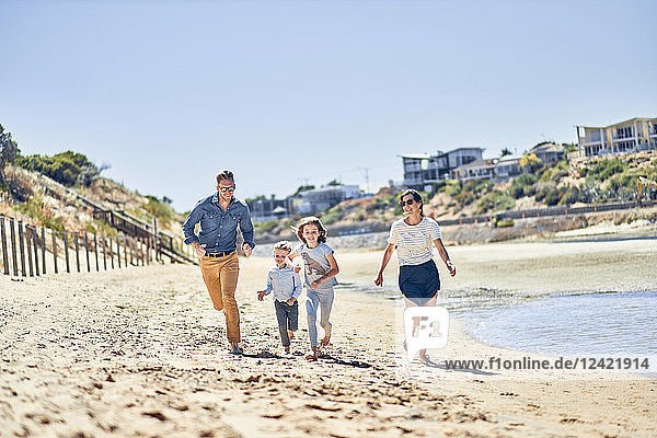 Australia  Adelaide  Onkaparinga River  happy family running on the beach together