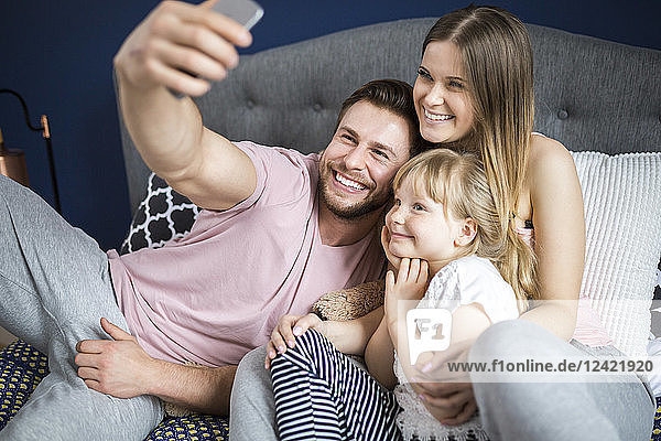 Happy family sitting on bed  taking smartphone selfies