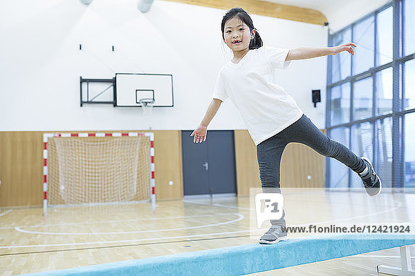 Schoolgirl balancing on balance beam in gym class