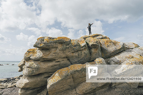 France  Brittany  Meneham  woman standing on rock formation at the coast