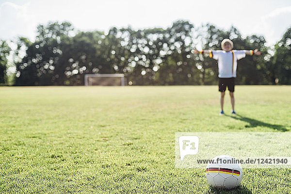 Boy with outstretched arms standing on soccer field between German soccer ball and goal