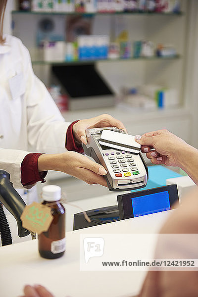Customer paying cashless with credit card in a pharmacy Customer paying cashless with credit card in a pharmacy