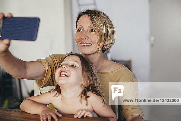 Portrait of mother and little daughter taking selfie with smartphone