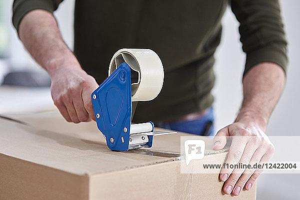 Close-up of man taping cardboard box Close-up of man taping cardboard box
