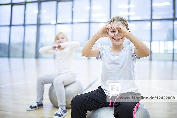 Portrait of smiling schoolgirls sitting on gym balls in gym class