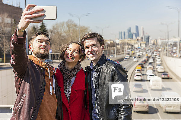 Russia  Moscow  friends taking a selfie in the city  road in the background