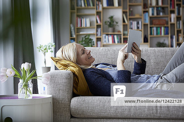 Woman using digital tablet  relaxing on couch