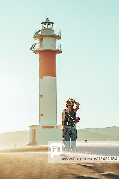 Young woman with windswept hair standing in desert landscape at lighthouse