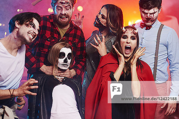 Friends in creepy costumes having fun at Halloween party Friends in creepy costumes having fun at Halloween party