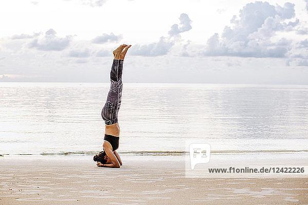 Thailand  Koh Phangan  Sportive woman doing yoga on the beach