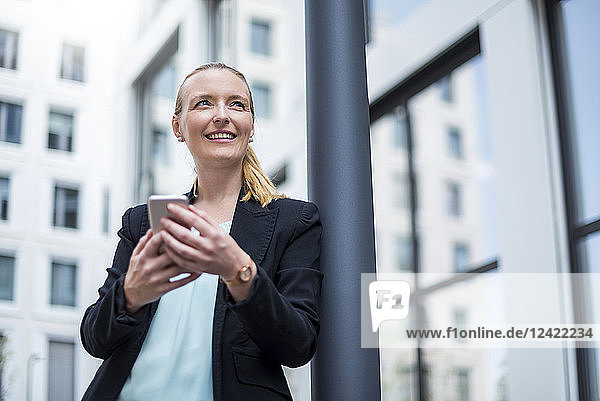 Portrait of smiling businesswoman with cell phone waiting