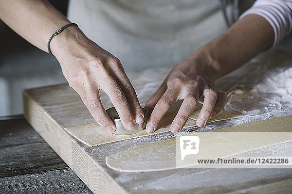 Woman preparing ravioli  pasta dough cutting out on pastry board
