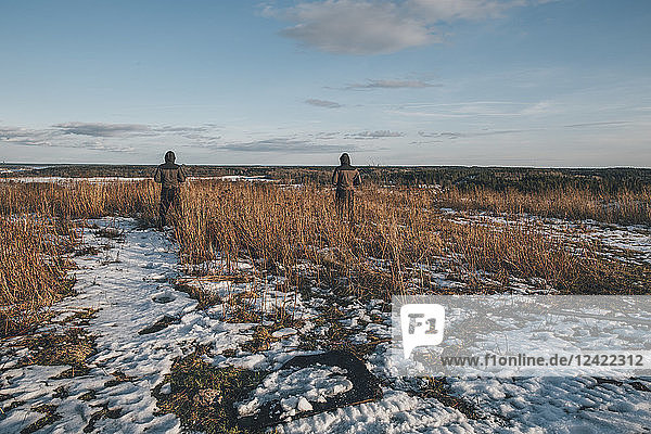 Sweden  Sodermanland  two men standing in remote landscape in winter
