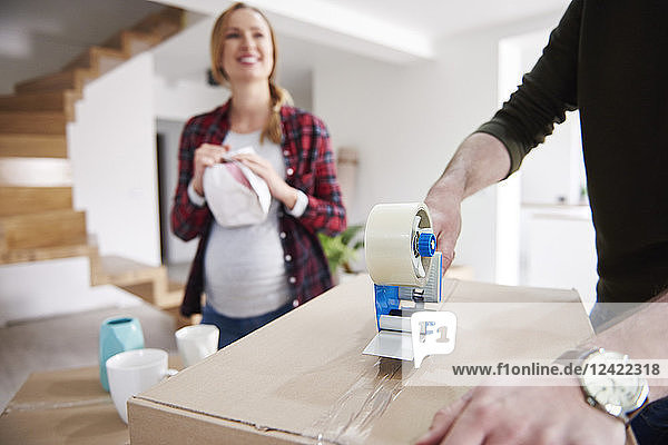Couple moving house packing and taping cardboard boxes Couple moving house packing and taping cardboard boxes