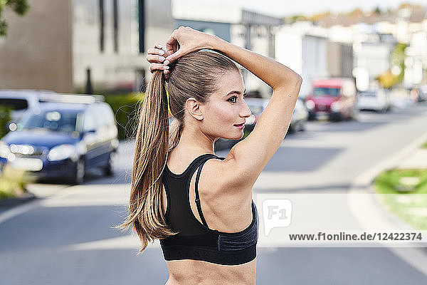 Attractive sportive young woman on a street in the city