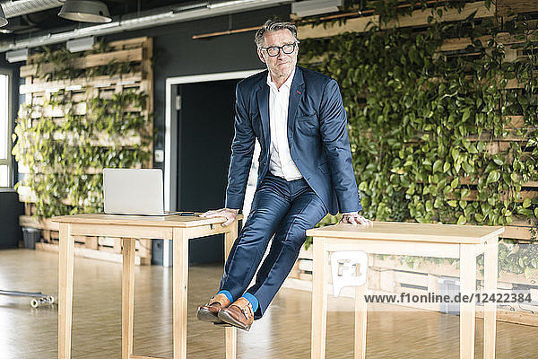 Mature businessman leaning on tables in green office