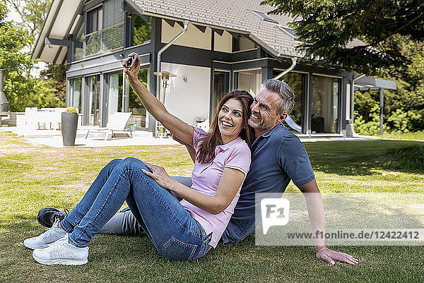 Happy couple sitting in garden of their home taking a selfie
