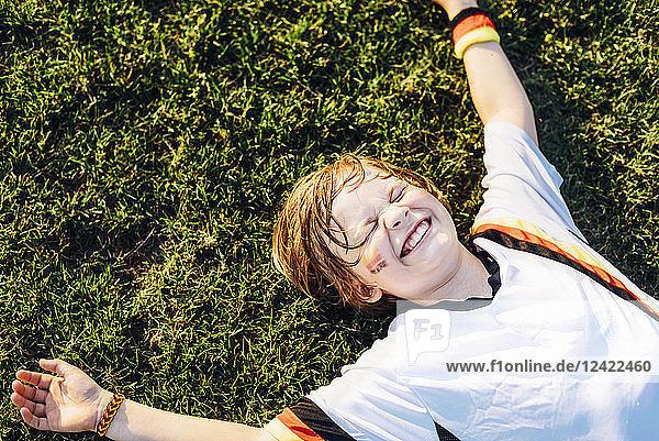 Boy in German soccer shirt lying on grass  laughimg