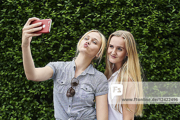 Two young women posing for a selfie at a hedge