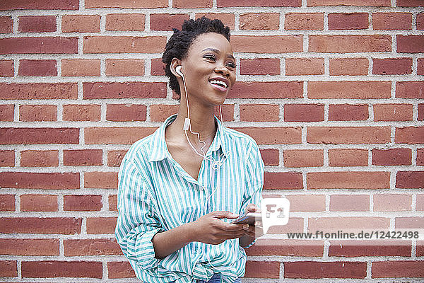 Portrait of relaxed woman using earphones and cell phone Portrait of relaxed woman using earphones and cell phone