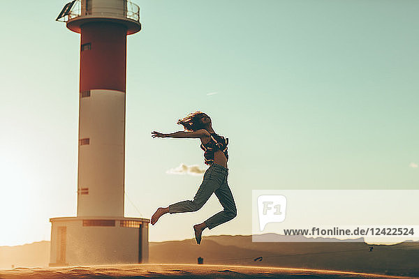 Young woman jumping in desert landscape at lighthouse