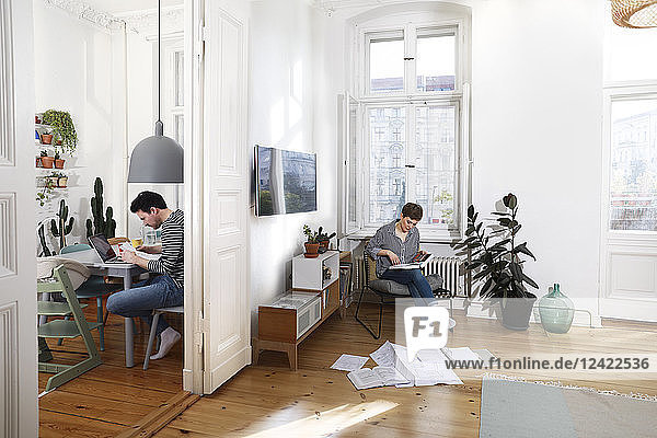 Couple sitting at home  sorting files with documents