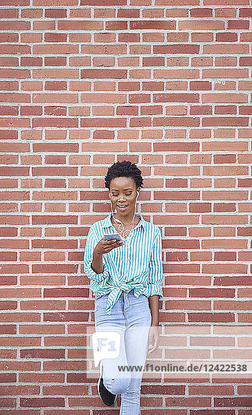 Smiling woman leaning against brick wall using earphones and cell phone Smiling woman leaning against brick wall using earphones and cell phone