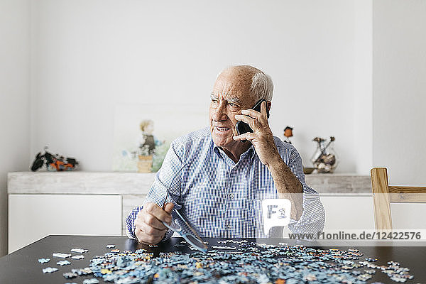 Happy senior man using smartphone while doing a puzzle at home