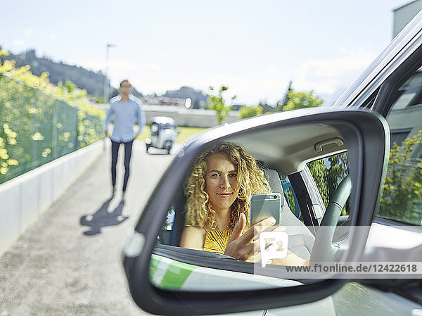 Smiling young woman using cell phone in electric car