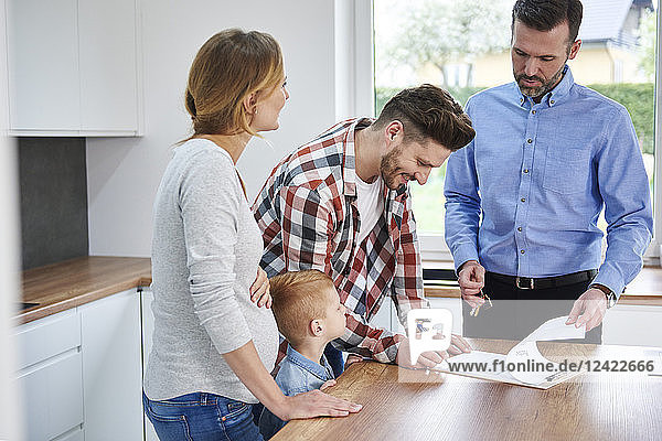 Family with real estate agent signing contract in kitchen of new apartment Family with real estate agent signing contract in kitchen of new apartment