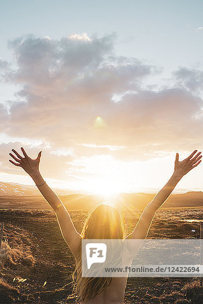 Iceland,  young woman with raised arms at sunset