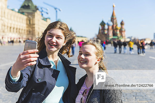 Russia  Moscow  Two teenage girls taking a selfie on the Red Square in the city
