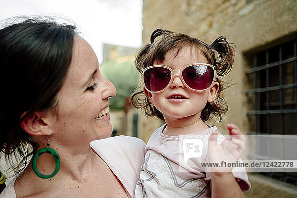 Happy baby girl wearing mother's sun glasses