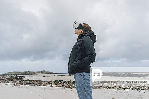France  Brittany  Landeda  young woman standing at the coast wearing VR glasses