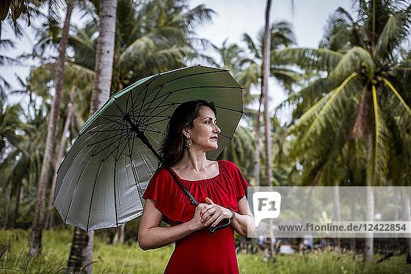 Thailand  Koh Phangan  portrait of woman strolling with umbrella