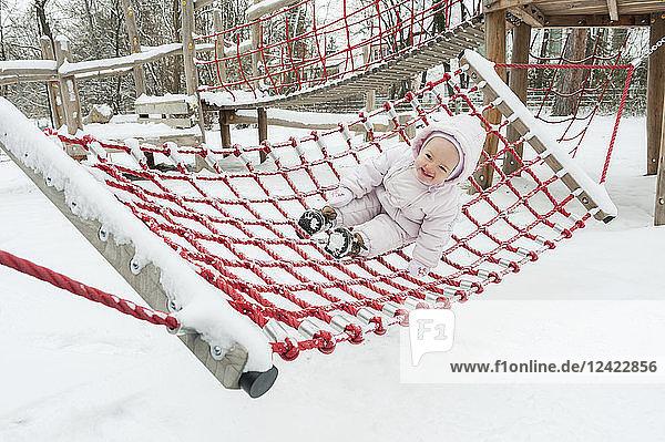 Baby girl having fun on swing in winter