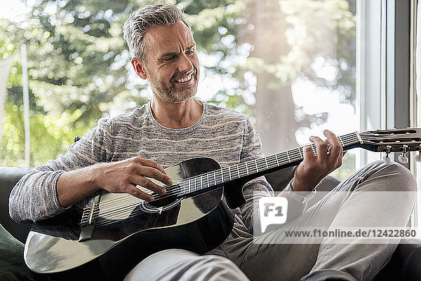 Happy mature man lying on couch at home playing guitar