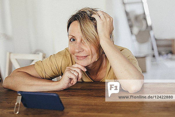 Portrait of smiling woman sitting at table with smartphone in new flat