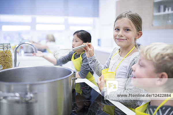 Portrait of smiling schoolgirl with classmtes in cooking class
