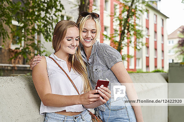 Two happy young women sharing cell phone outdoors