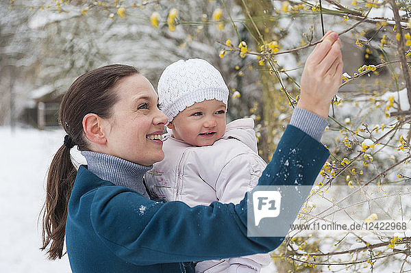 Portrait of happy mother with baby girl in snow-covered landscape