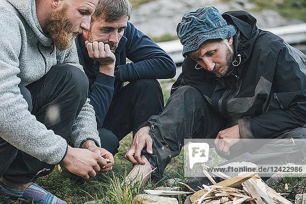 Norway  Lofoten  Moskenesoy  Young men starting a camp fire