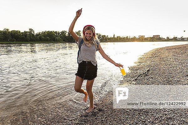 Young woman walking barefoot on riverside  earphones and smartphone